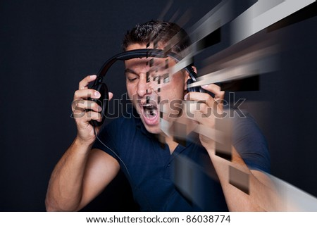 Man yelling while listening to headphones in black background with squares coming out of the face - stock photo