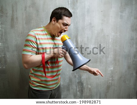 man yells into a megaphone and points down on the gray textured background wall. - stock photo