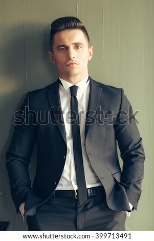Man young handsome sensual elegant model in suit with skinny necktie open coat draws back against wall hands in pockets looks in camera vintage on grey background  - stock photo