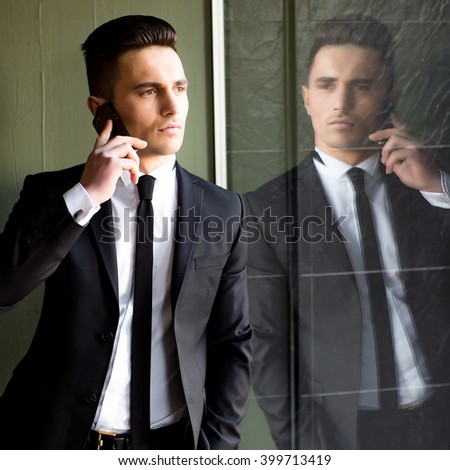 Man young handsome sensual elegant model in suit with skinny necktie open coat talks on mobile phone looks away hand in pocket reflects in mirror on grey background  - stock photo
