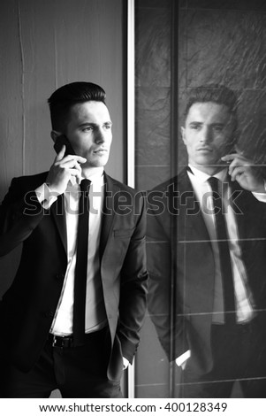 Man young handsome sensual elegant model in suit with skinny necktie open coat talks on mobile phone looks away hand in pocket reflects in mirror black and white on grey background  - stock photo