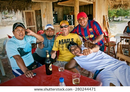MANABI, ECUADOR - DECEMBER 18, 2011: Group of male friends drinking beer in a bungalow by the beach, Puerto Lopez. - stock photo