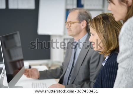 management team with middle-aged man and two business women watching the computer screen