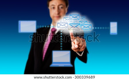 Manager accessing email via a virtual network of smart devices. Laptop, cellphone and tablet computer all link to a cloud formed by many email icons. Metaphor for connectivity and smart computing. - stock photo