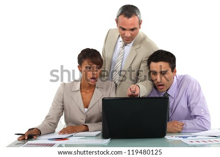 Manager and his shocked employees looking at a laptop - stock photo