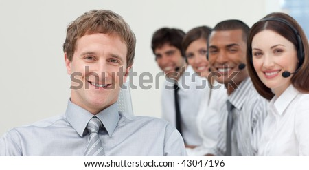 Manager and his team smiling at the camera in a call center - stock photo
