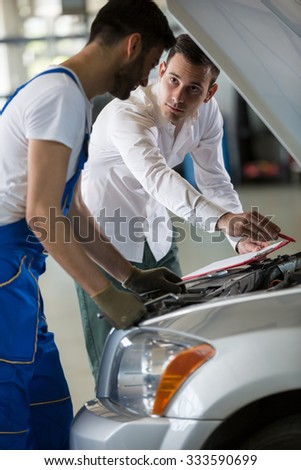 manager and mechanic examine a car damage - stock photo