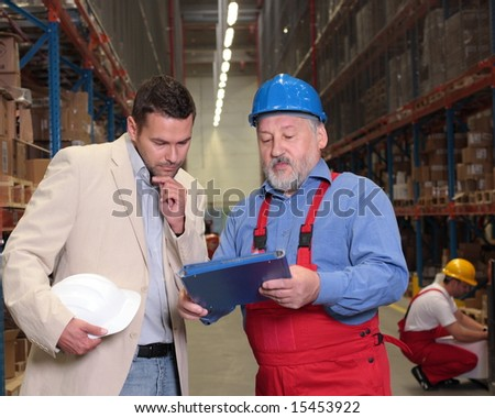 manager and older worker browsing papers in warehouse - stock photo