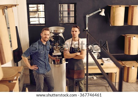 Manager and owner of a coffee roastery with roasting machine - stock photo