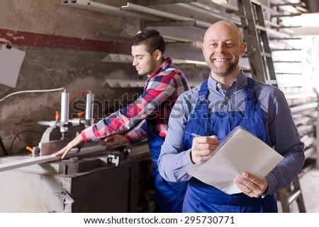 manager and young worker approving work at PVC windows factory - stock photo