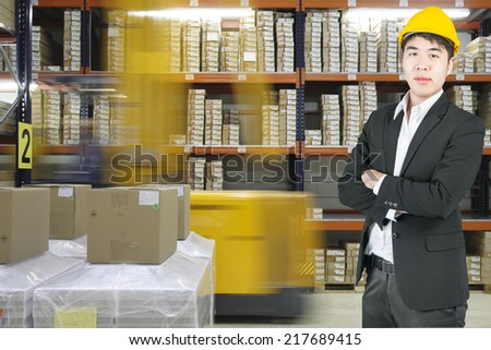 Manager asian business in modern warehouse - stock photo
