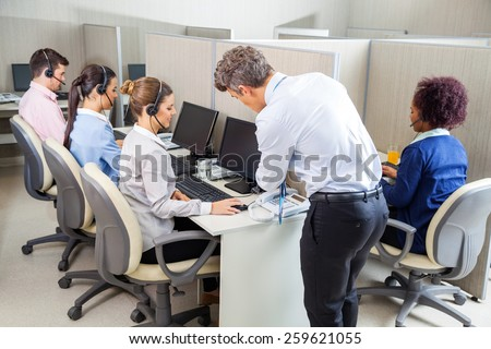 Manager assisting young female customer service agent while employees working in call center - stock photo