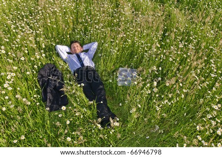 Manager, Business man lying in the middle of a field of flowers and more relaxed, his jacket is next to him - stock photo