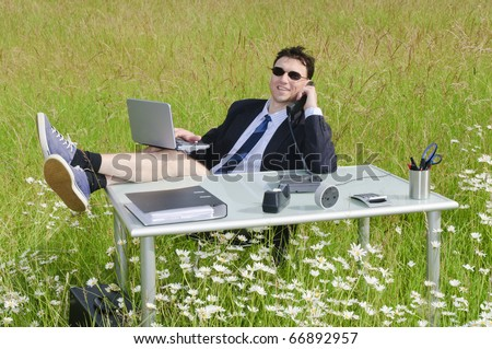 Manager, Business man sitting at a desk in the middle of a meadow in shorts and relax. - stock photo