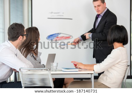 Manager delivering a presentation to business people in company environment - stock photo