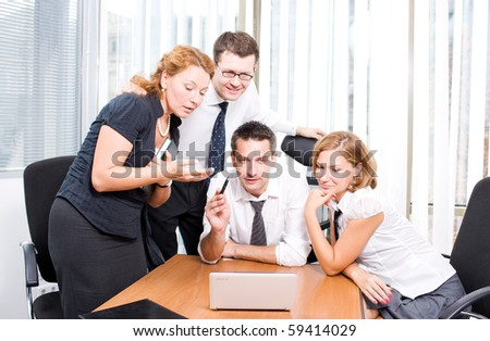 Manager demonstrating new business strategy of their company while sitting during meeting in board room Hi Res. Office workers looking at the laptop computer's screen very attentively. - stock photo