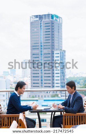 Manager discussing business ideas while sitting in the rooftop cafe - stock photo