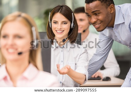 Manager explaining something to his employee in a call centre. - stock photo
