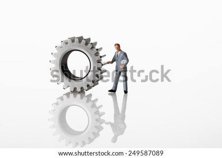 Manager figurine standing with cogwheels on white background