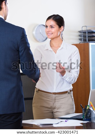 Manager greeting new caucasian employee and smiling in office - stock photo