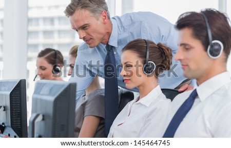 Manager helping call centre agent on a computer - stock photo