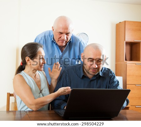 Manager helping to senior couple with laptop - stock photo