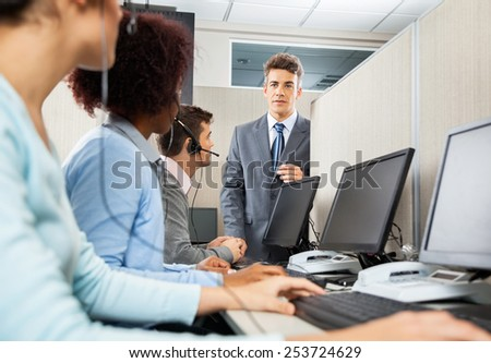 Manager in discussion with customer service representatives in office - stock photo