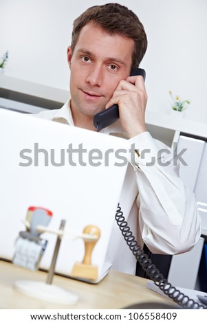 Manager in office making a phone call at his desk - stock photo