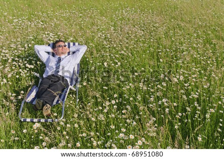 Manager in the Open and is relaxed on a striped deck chair on a lazy meadow - stock photo