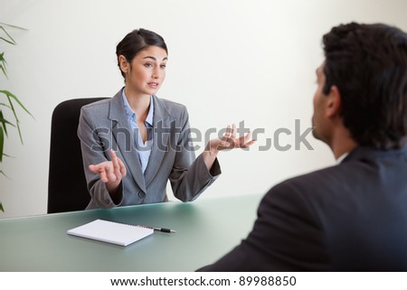 Manager interviewing an employee in her office - stock photo