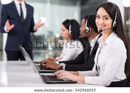 Manager is explaining something to employees in a call centre - stock photo