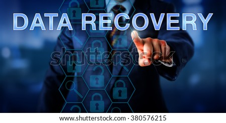 Manager is pointing at DATA RECOVERY on a touch screen. Business metaphor and technology concept. Magnifier glass icons do reference analyzing tools and locked padlocks represent encrypted files. - stock photo