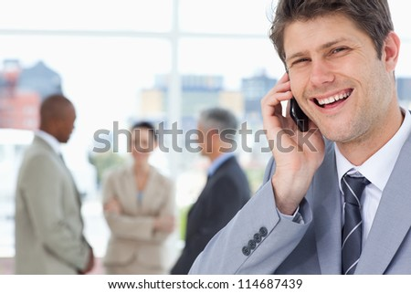Manager laughing while using his mobile phone - stock photo