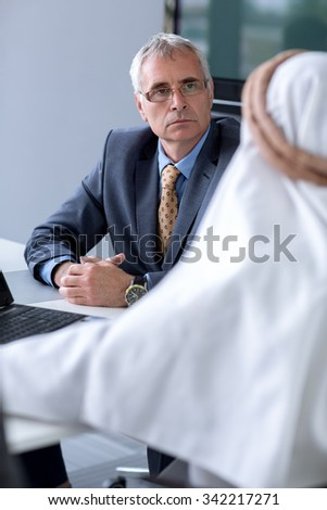 Manager of company listen Arabian guest about their serious situation - stock photo