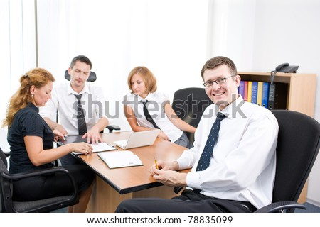 Manager on meeting with office workers in board room - stock photo