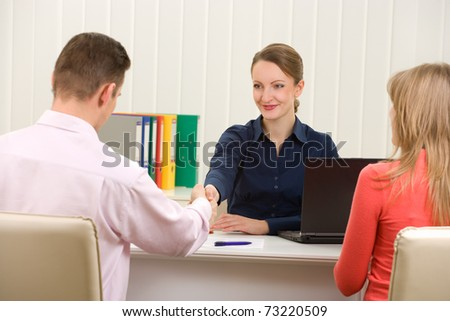 Manager (or notary public) greeting with couple - stock photo