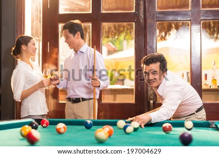 Manager playing pool during the party - stock photo
