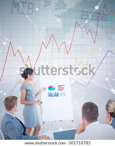 Manager presenting statistics to her colleagues against stocks and shares - stock photo