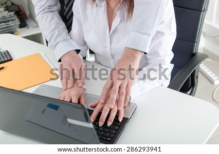Manager putting his hands on the hands of his secretary, at office
