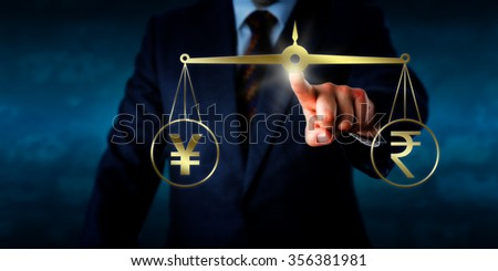 Manager quoting the Indian rupee at par with the Chinese yuan or Japanese yen. His left index finger is keeping a golden pair of scales in temporary equilibrium. Concept of foreign currency exchange. - stock photo