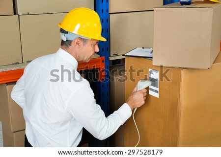 Manager Scanning Label On Cardboard Box With Barcode Scanner In Warehouse - stock photo