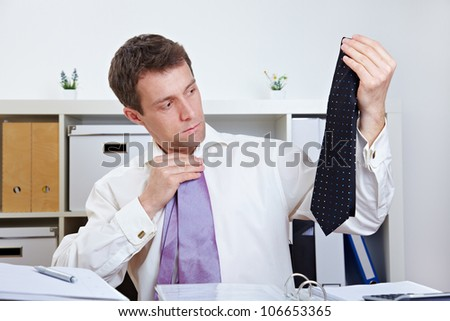 Manager selecting a tie at his desk in the office - stock photo