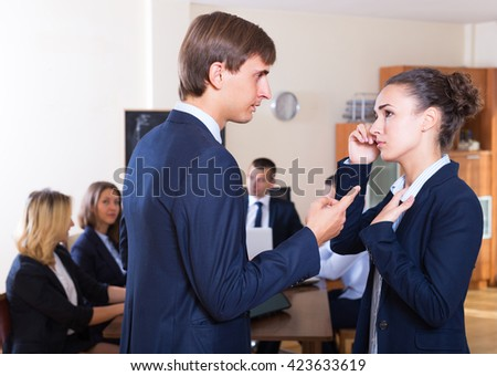 Manager severely lecturing female employee for mistake at office meeting. Focus on man