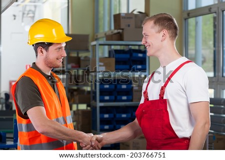 Manager shaking hands with factory worker, horizontal