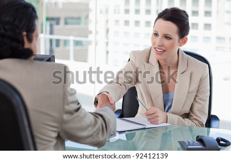 Manager shaking the hand of a male applicant in her office - stock photo
