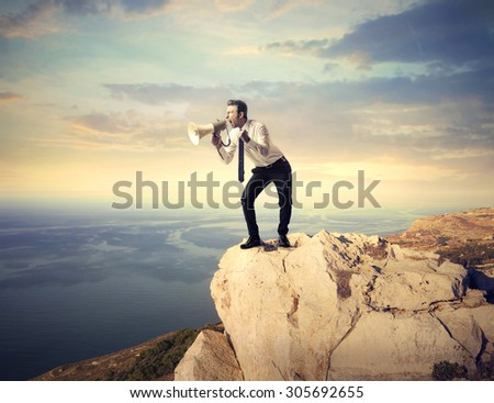 Manager shouting his message from a steep rock