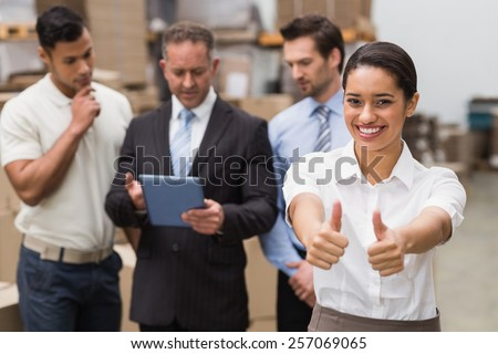 Manager showing thumbs up in front of her colleagues in a large warehouse - stock photo