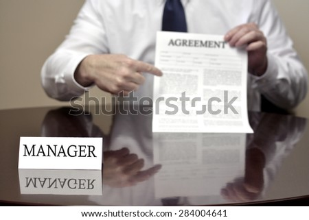 Manager sitting at desk holding Agreement document for deal