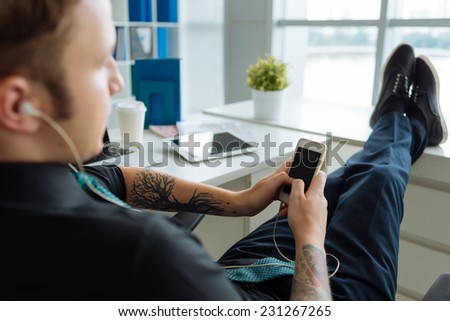 Manager sitting with his legs on the window-sill and text messaging - stock photo