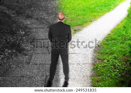 Manager standing at a crossroad - decision making concept - stock photo
